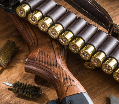 winchester: Hunting equipment - pump action shotgun, 12 guage cartridge  and hunting knife on the wooden table.