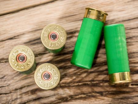 木製テーブルの上ポンプ散弾銃の 12 ゲージのカートリッジ。