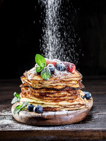 Pancakes with fresh berries on the wooden table. Stock Photo