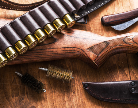 Hunting equipment - pump action shotgun, 12 guage cartridge and hunting knife on the wooden table. Stock Photo