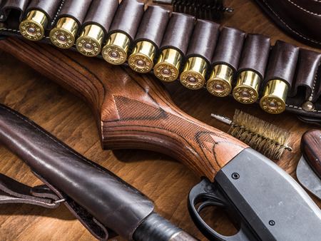 winchester: Hunting equipment - pump action shotgun, 12 guage cartridge and hunting knife on the wooden table. Stock Photo
