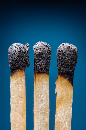 burned out: Burnt out safety matches. Blue background.