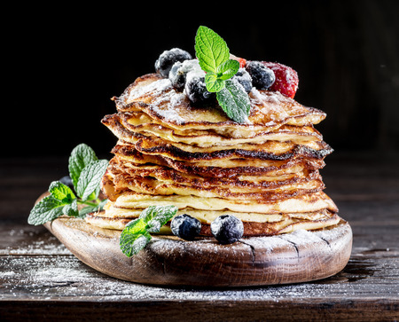 Pancakes with fresh berries on the wooden table. 写真素材