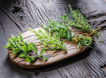 Different bunches of fresh herbs on the wooden table. Stock Photo