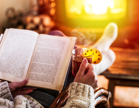 Hot mulled wine and book in woman hands. Relaxing in front of burning fire in the cold winter day. Stock Photo