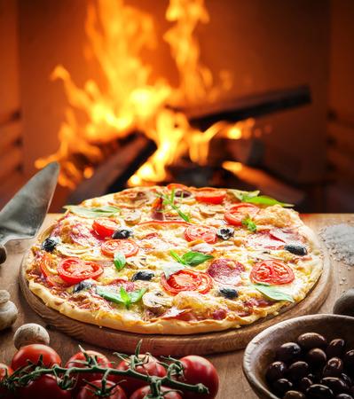 ピザ。背景に薪のオーブン。