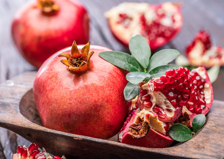 Ripe pomegranate fruits on the wooden background. Macro.
