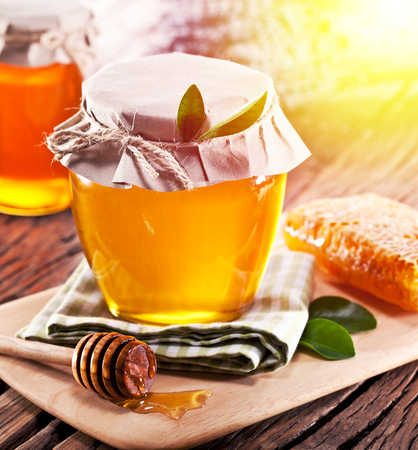Jar full of fresh honey and honeycombs. Colorful nature background.