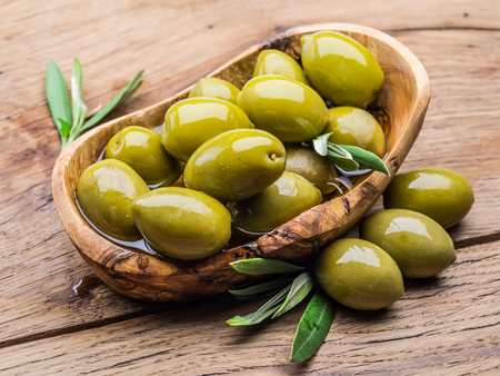 Whole table olives in the wooden bowl on the table. Stock Photo