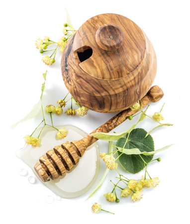 Wooden pot full of fresh linden honey and linden flowers. Stock Photo