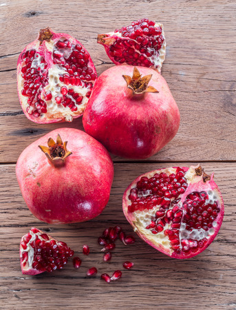 Ripe pomegranate fruits on the wooden background. Top view.