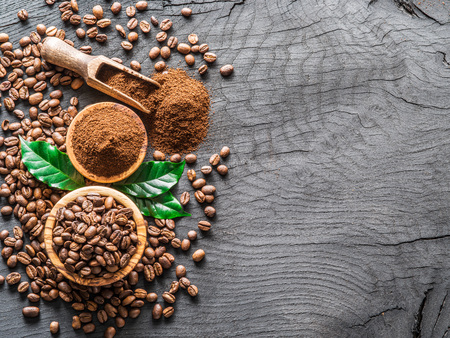 Roasted coffee beans  and ground coffee on wooden table. Top view.