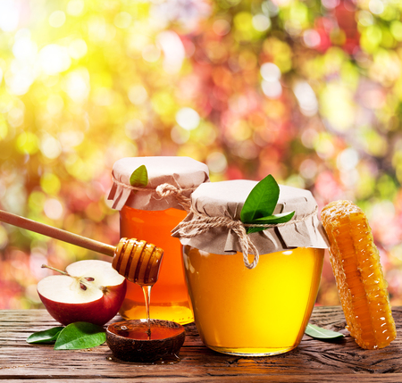 Jars full of fresh honey and honeycombs. Colorful nature background.