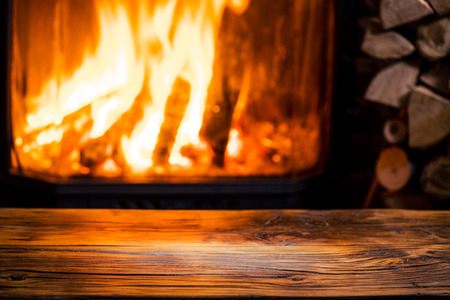 Old wooden table and fireplace with warm fire at the background.