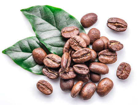 Roasted coffee beans and leaves on white background. Imagens