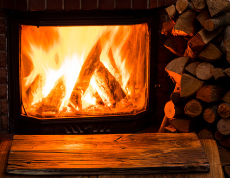 Empty wooden table and fireplace with warm fire at the background.