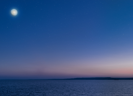 Moon and stars over the calm sea.