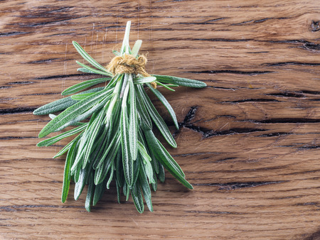 Bunch of rosemary herb on the wooden table. Standard-Bild