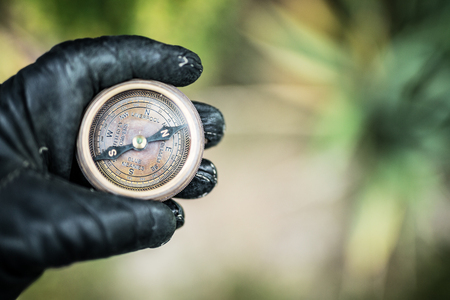 Mans hand in a leather glove holding a compass. Nature background. Standard-Bild