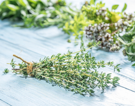 Different bunches of fresh herbs on the wooden table. Standard-Bild
