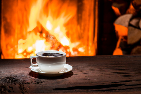 Cup of hot coffee on the wooden table and fireplace at the background. Standard-Bild
