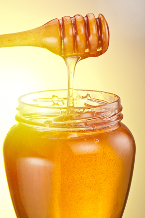 Jar full of fresh honey and honey dipping from wooden spoon into the jar.