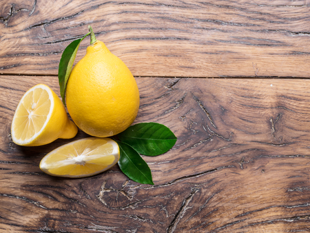 Ripe lemon with lemon leaves on old wooden table. Close-up.