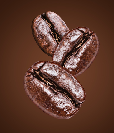 Three roasted coffee beans on the brown background. File clipping path.