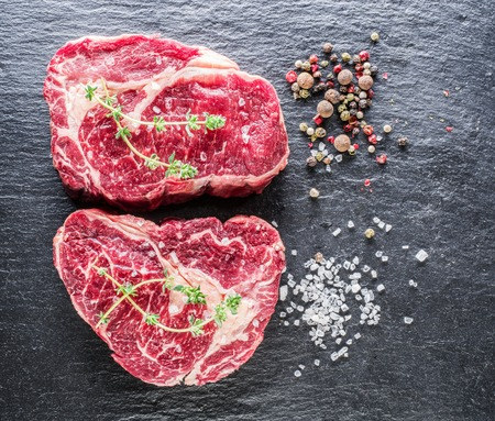 Rib eye steaks with spices on the black background.  Stockfoto