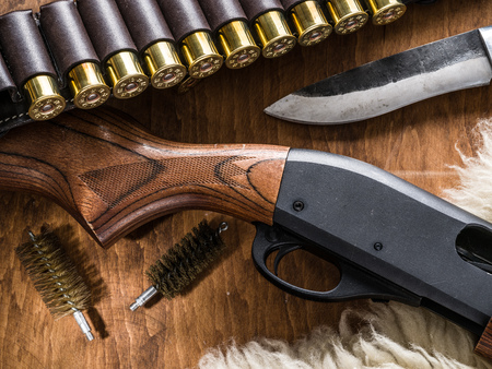 Hunting equipment - pump action shotgun, cartridge 12 guage and hunting knife on the wooden table.