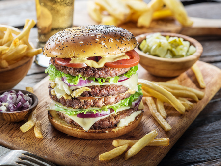 Big hamburger and French fries on the wooden tray. Stock Photo