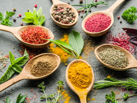 Assortment of colorful spices in the wooden spoons. Stock Photo