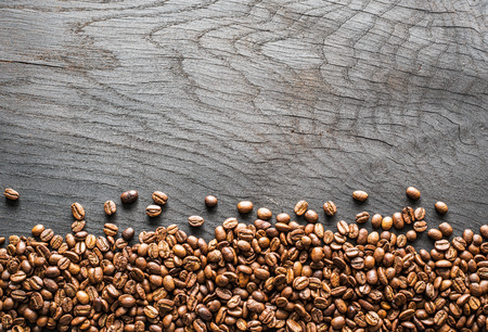 Roasted coffee beans on wooden table. Top view.