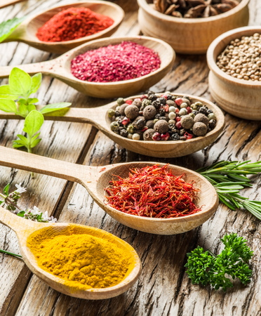Assortment of colorful spices in the wooden spoons on the wooden table. Stock Photo
