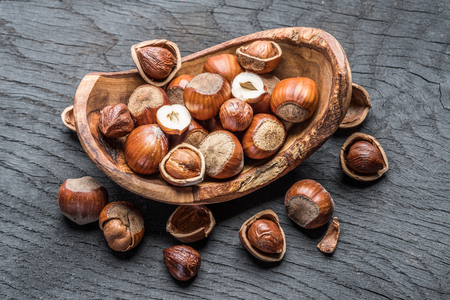 Filberts or hazelnuts in the wooden bowl on the table. Top view. Фото со стока