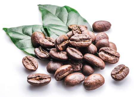Roasted coffee beans and leaves on white background. Stock fotó