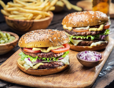 Hamburgers and French fries on the wooden tray. Stock Photo