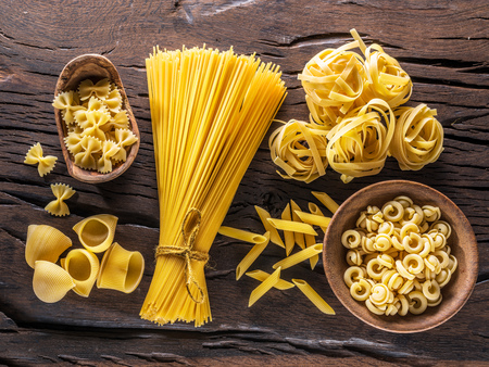 Different pasta types on the wooden table. Top view. Stockfoto