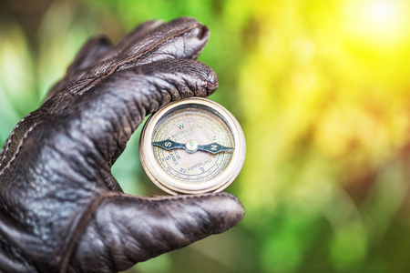 Mans hand in a leather glove holding a compass. Nature background. Stock Photo