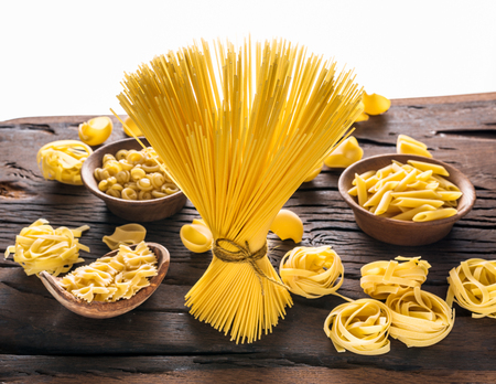 Different pasta types on wooden table. White background. Stockfoto