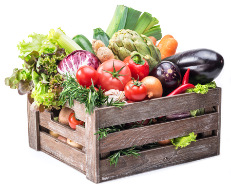 Fresh multi-colored vegetables in wooden crate. White background. Stock Photo
