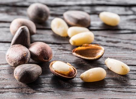 Pine nuts on dark wooden table. Organic food. Macro.