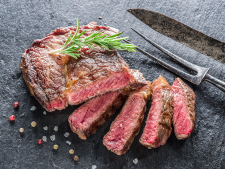 Medium Ribeye steak with spices on the graphite tray. Stockfoto