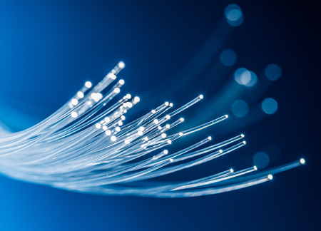 Bundle of optical fibers with lights in the ends. Blue background.