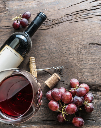 Wine glass, wine bottle and grapes on wooden background.