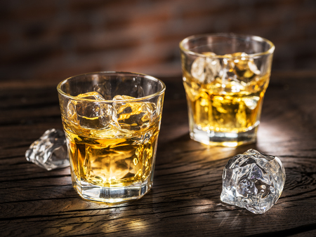 Whiskey glasses or glasses of whiskey with ice cubes on the wooden table.