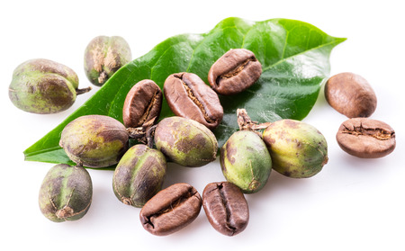 Green coffee beans, roasted beans and fresh coffee leaves on white background. Macro. Imagens