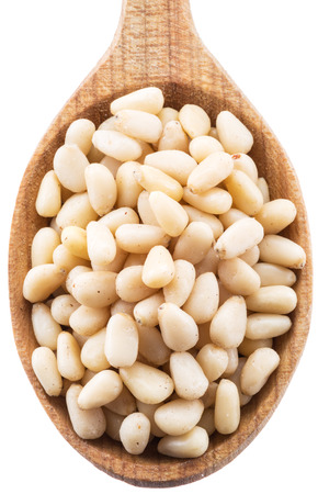 Pine nuts in the wooden spoon. White background.