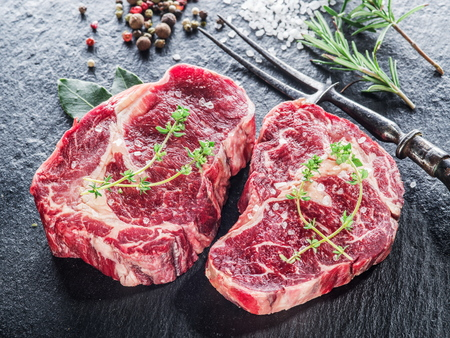Rib eye steak with spices on the black background. Stockfoto