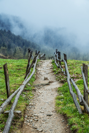The Dolomites Alps. The fenced path in the mountain hills. Tops of mountains covered with clouds at the background. Banque d'images - 116655106